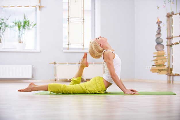 Beautiful sporty fit yogi woman practices yoga lying asana ardha bhujangasana in the fitness room