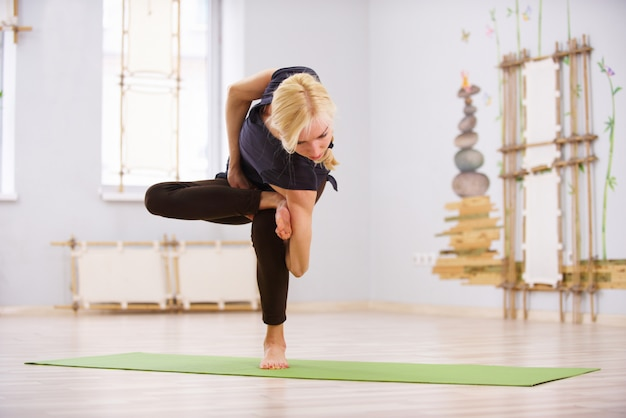 Beautiful sporty fit yogi woman practices yoga twist asana in the fitness room