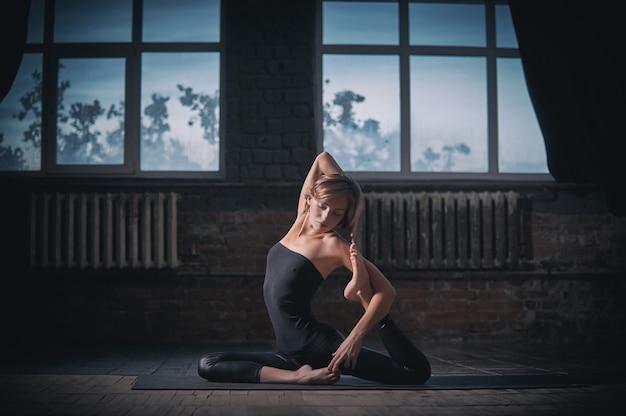 Красивая спортивная девушка-йогиня занимается йогой асаной eka pada rajakapotasana в темном зале
