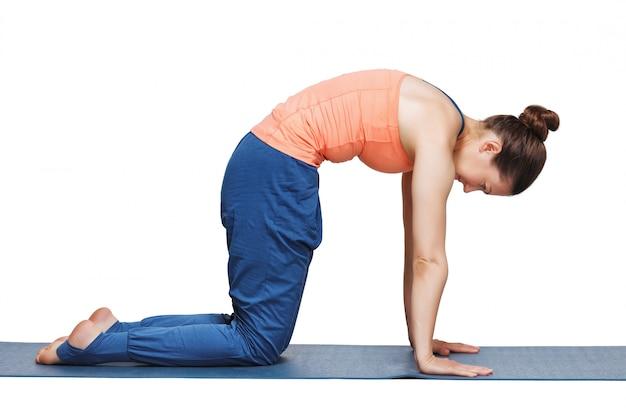 Beautiful sporty fit yogini woman practices yoga asana marjariasana