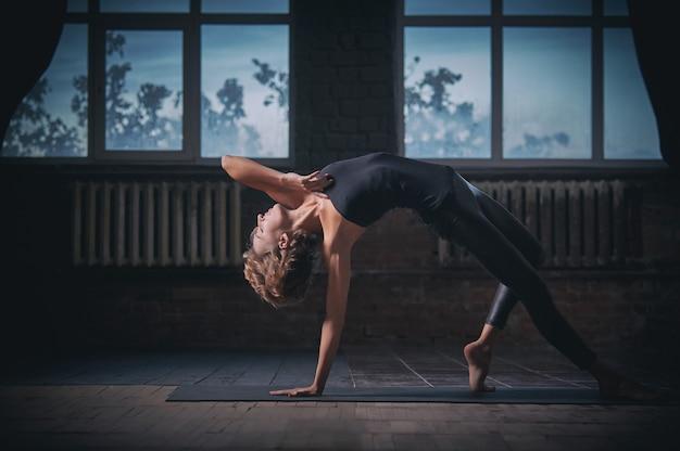 Красивая спортивная девушка-йогиня занимается йогой асаной wild thing pose в темном зале