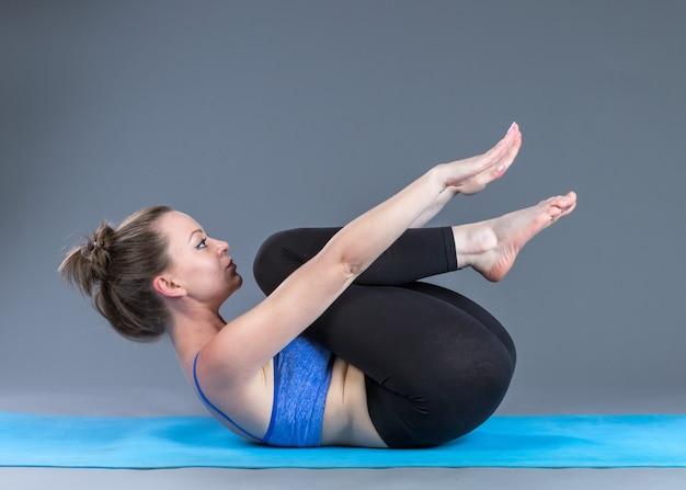 Красивая спортивная пригонка молодая женщина практикует асаны йоги.