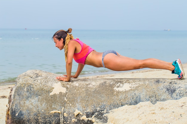 Beautiful sporty girl on the beach sports