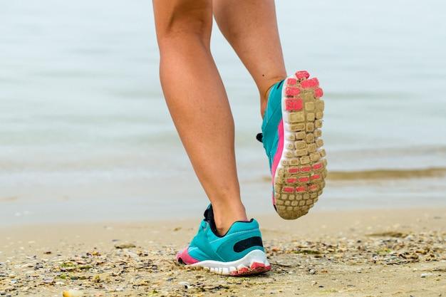 Bella ragazza sportiva sulla spiaggia