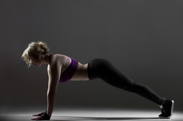 Beautiful sporty girl doing push-ups
