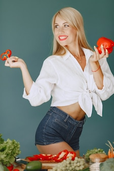 Beautiful and sporty girl in a kitchen with a vegetables