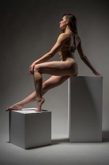 Красивая спортивная девушка позирует на кубиках