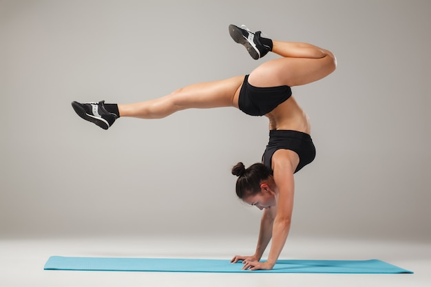 Beautiful sporty girl standing in acrobat pose