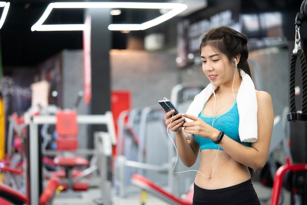 Beautiful sporty girl with earphones and smartphone walking or running on treadmill at gym
