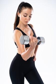 白で隔離される2つのダンベルで運動する美しいスポーティな筋肉の女性