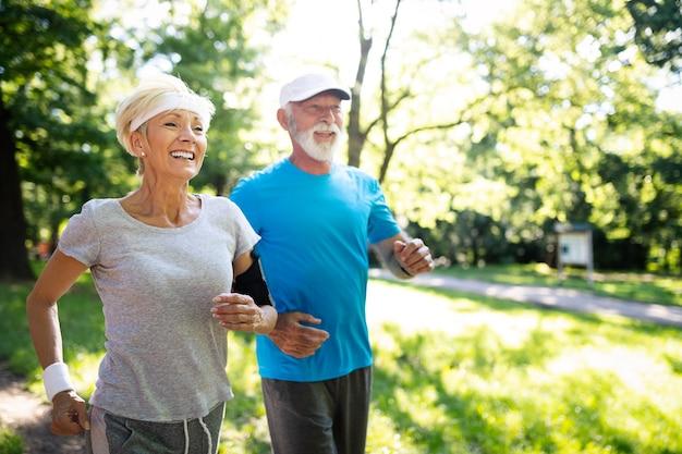 Красивая спортивная старшая пара, оставаясь в форме с бегом и бегом трусцой