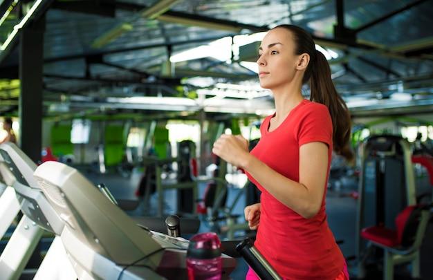 Красивая спортивная стройная молодая женщина в фитнес-одежде бегает на беговой дорожке в тренажерном зале.