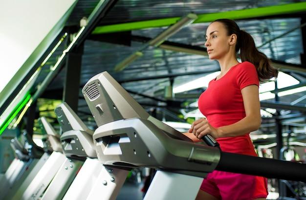 フィットネスウェアの美しいスポーティなスリムな若い女性がジムのトレッドミルでジョギングしています。