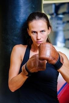 ジムで赤いサンドバッグとボクシングの美しいスポーティな女性