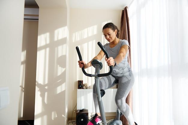 Beautiful sporty woman cycling a bike at home