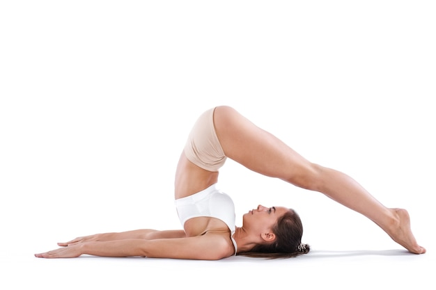 Красивая спортивная женщина делает упражнения на растяжку. изолированные на белом.