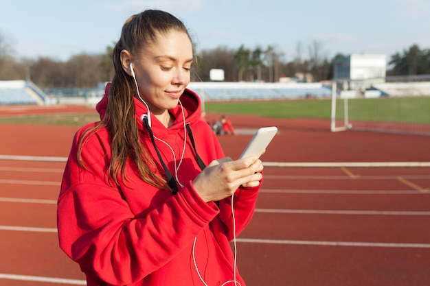 Beautiful sporty woman to fashionable red hoodie listens to music in headphones through smartphone