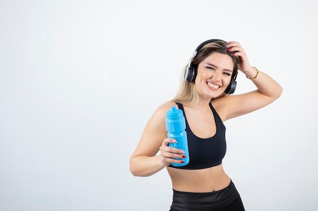 Bella donna sportiva in cuffie che tengono bottiglia con acqua.