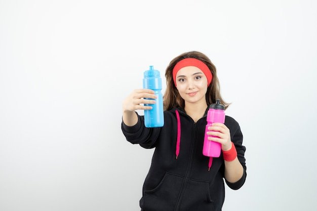 白い壁に水とボトルを保持している美しいスポーティな女性。