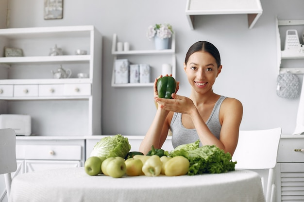 Beautiful and sporty woman in a kitchen with vegetables