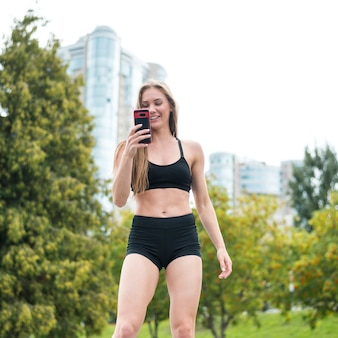 Beautiful sporty woman looking at the phone