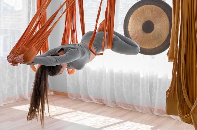 Красивая спортивная женщина практикует летную йогу в гамаке, балансируя и растягивая спину