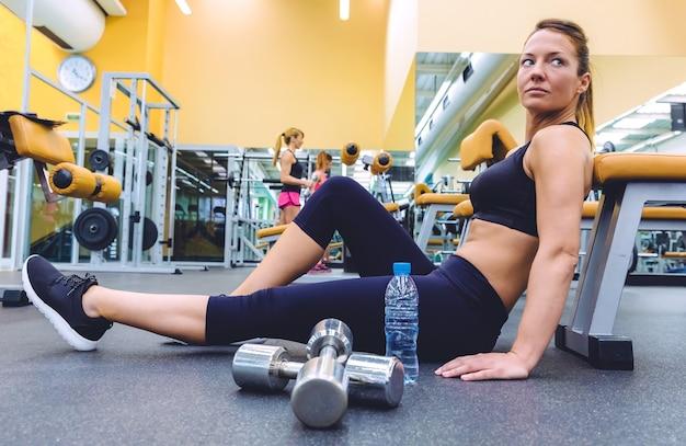 フィットネスセンターの床に座って休んでいる美しいスポーティな女性とダンベルで運動をしている人々