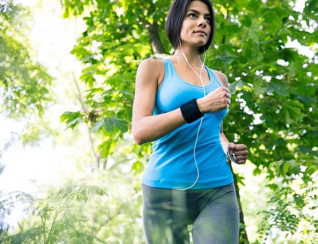 公園で走っている美しいスポーティな女性