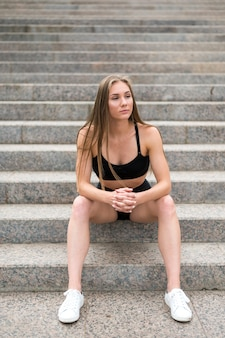Beautiful sporty woman sitting on stairs and looking away