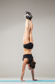 Beautiful sporty woman standing in acrobat pose