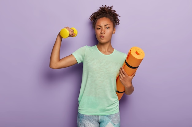 Beautiful sporty woman trains biceps, raises dumbbell