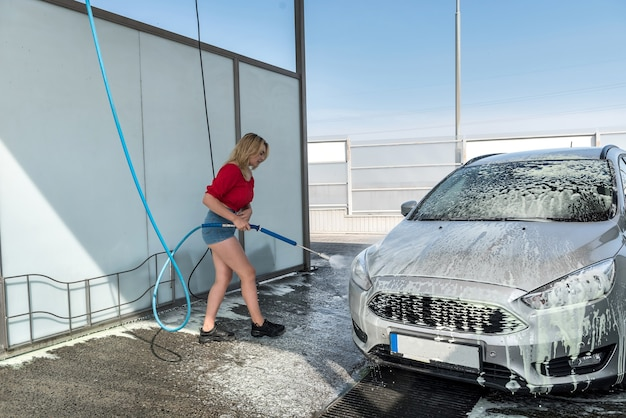 Beautiful sporty woman washes auto with foam at car wash