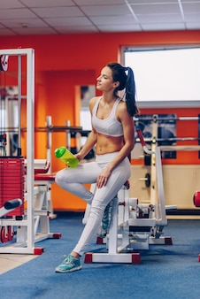 Beautiful sporty woman with perfect body keeps the shaker bottle in hand in the gym