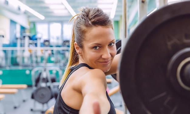 Красивая спортивная женщина с большими пальцами руки улыбается и отдыхает над штангой после мышечной тренировки в фитнес-центре