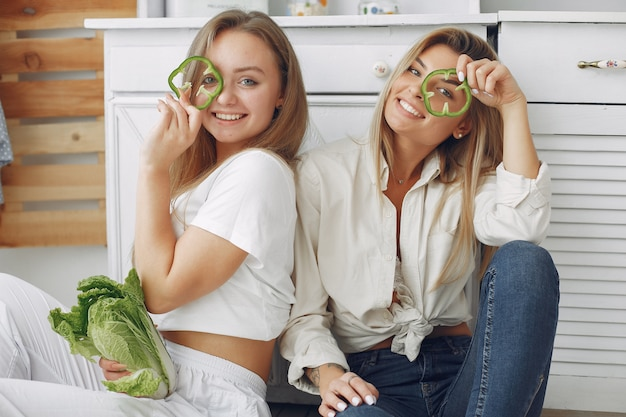 Beautiful and sporty women in a kitchen with vegetables