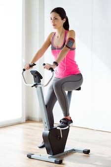 Beautiful sporty young woman doing exercise in gym.