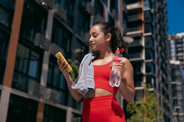 赤いトップとレギンスを着てトレーニングやジョギングの後に休憩を取っている茶色の髪の美しいスポーティな若い女性
