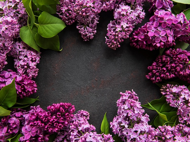 Beautiful spring flowers lilac on dark stone background with place for text. syringa vulgaris. happy mother's day greetings card. top view. copy space.