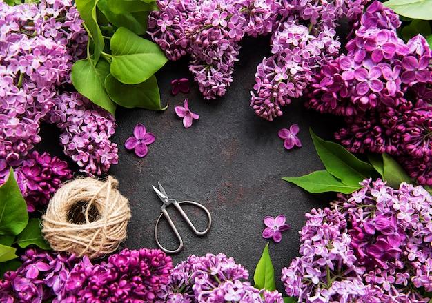 はさみと糸で暗い石の表面に美しい春の花ライラック