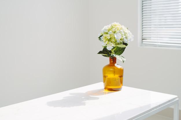 Beautiful spring flowers in vase on window background.