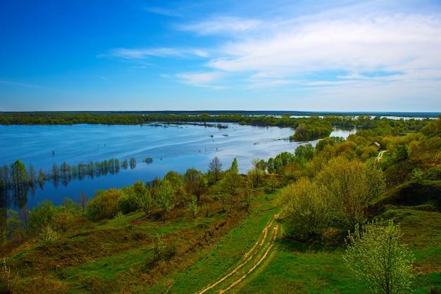 높은 언덕에서 아름 다운 봄 풍경입니다. 언덕에서 홍수의 놀라운 전망. 유럽. 우크라이나. 흰 구름과 인상적인 푸른 하늘