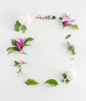 Beautiful spring letter frame made of flowers. magnolia, roses, and leaves on bright background.