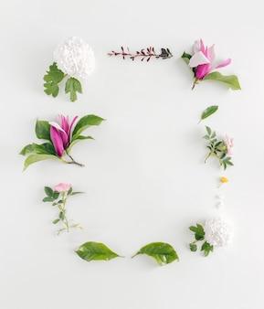 꽃으로 만든 아름다운 봄 편지 프레임입니다. 목련, 장미, 그리고 밝은 배경에 나뭇잎.