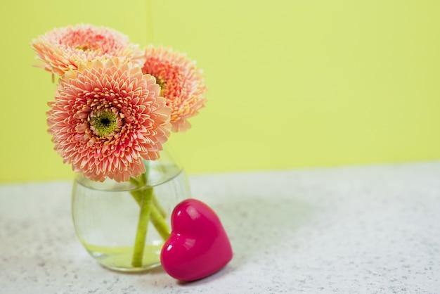 花瓶の青いパステル調のテーブルの上の美しい春のピンクの花。花のボーダー。