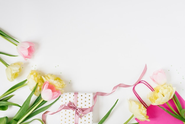 Beautiful spring pink and yellow tulips flowers with white ribbon with bright bag on white flat lay womans day or valentines day gift concept of holiday spring sale in store or online shopping
