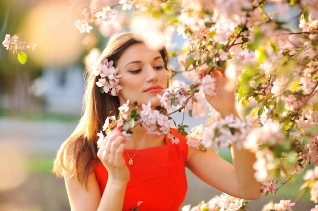 Beautiful spring woman with blossom apple tree flowers