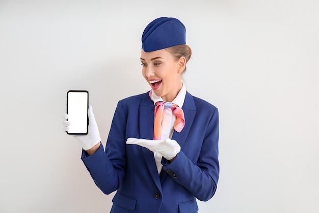 明るい空間で携帯電話を持つ美しいスチュワーデス