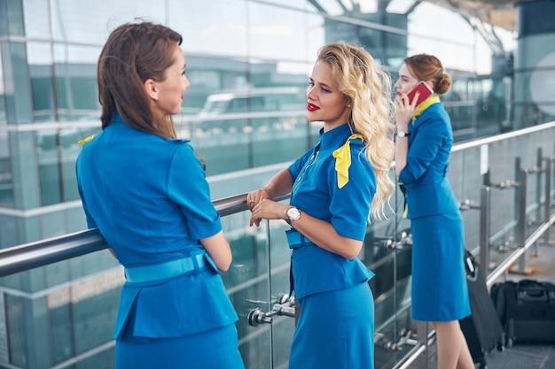 Красивые стюардессы в синей форме болтают в аэропорту, пока их коллега разговаривает по телефону