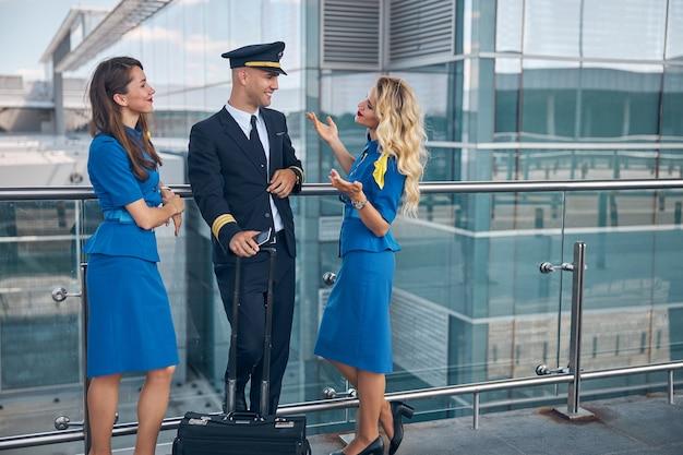 Красивые стюардессы в синей форме болтают с коллегой-мужчиной и улыбаются, пока мужчина держит мобильный телефон