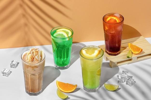 夏の飲み物の透明なグラス4杯の美しい静物画。ヤシの木の影と熱帯の背景にライム、ミント、レモン、柑橘類と緑のレモネード